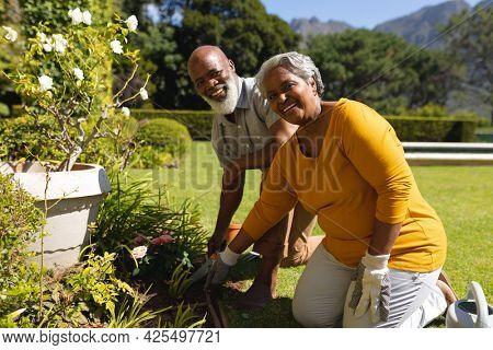 Portrait of senior african american couple spending time in sunny garden together planting flowers. retreat, retirement and happy senior lifestyle concept.