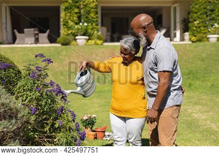 Senior african american couple spending time in sunny garden together watering flowers. retreat, retirement and happy senior lifestyle concept.