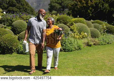 Senior african american couple spending time in sunny garden together walking and smiling. retreat, retirement and happy senior lifestyle concept.