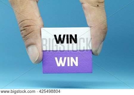 Hands Holding Colored Cubes And The Word Win, Win