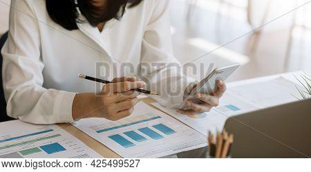 Young Woman Using Smart Phone And Checking Financial Report And Calculating Expenses In The Office