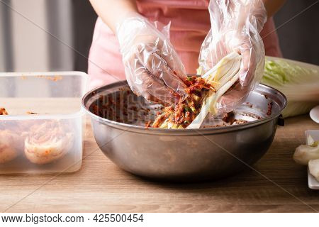Woman Making Kimchi Cabbage In A Big Bowl, Popular Homemade Korean Traditional Fermented Side Dish F
