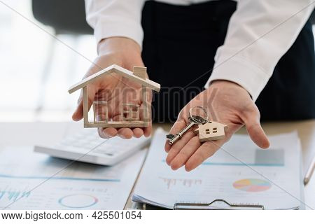 Real Estate Agent Giving House Key To The Client After Signing The Real Estate Contract. Home And Re