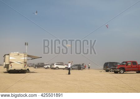 Port Aransas, Tx - 16 Feb 2020: Cars And Other Vehicles And People Flying Kites On A Hazy And Sandy