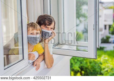 Extremly Tired Father And Son Looking Out The Window, Home Alone. Self-isolation At Home, Quarantine