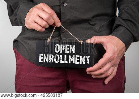 Open Enrollment Concept. Miniature Chalk Board In A Mans Hands