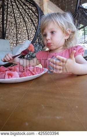 Little Girl Eating Watermelon On The Veranda Of A Country House