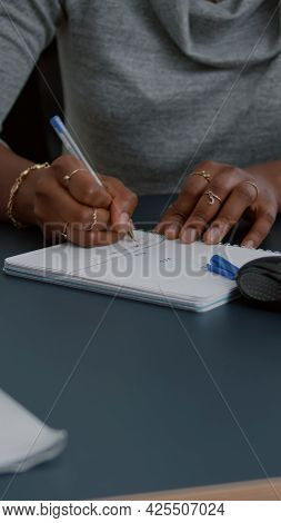 Closeup Of Student With Black Skin Writing Communication Homework On Notebook While Sitting At Desk