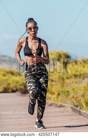 Afro American Woman Running On A Wooden Runway