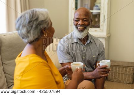 Senior african american couple sitting on sofa drinking coffee in living room. retreat, retirement and happy senior lifestyle concept.