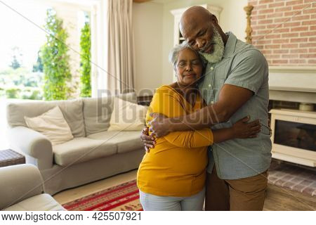 Senior african american couple embracing with eyes closed in living room. retreat, retirement and happy senior lifestyle concept.