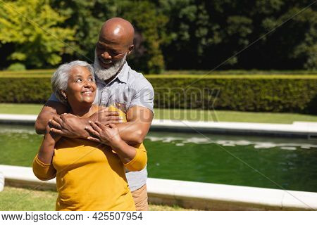 Senior african american couple spending time in sunny garden together embracing and smiling. retreat, retirement and happy senior lifestyle concept.