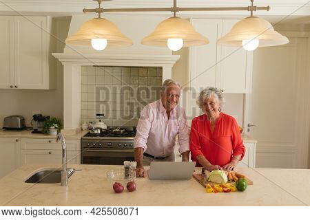 Portrait of senior caucasian couple cooking together and using laptop in kitchen. retreat, retirement and happy senior lifestyle concept.