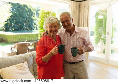 Portrait of senior caucasian couple looking at camera, smiling and holding mugs in living room. retreat, retirement and happy senior lifestyle concept.