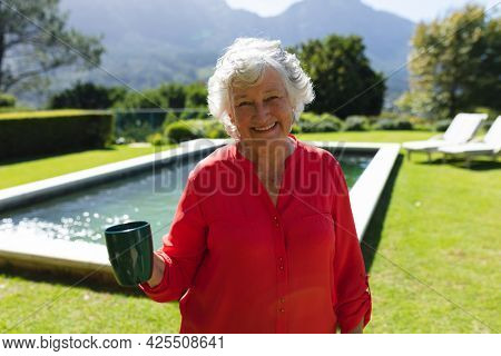 Portrait of senior caucasian woman smiling and holding mug in sunny garden. retreat, retirement and happy senior lifestyle concept.