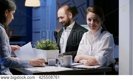 Portrait Of Focused Businesswoman Looking Into Camera Working In Office Meeting Room Late At Night.