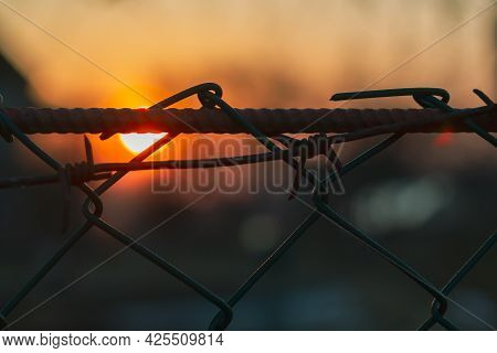 A Grating With Barbed Wire In The Evening At Sunset As A Symbol Of Imprisonment, Unfreedom.