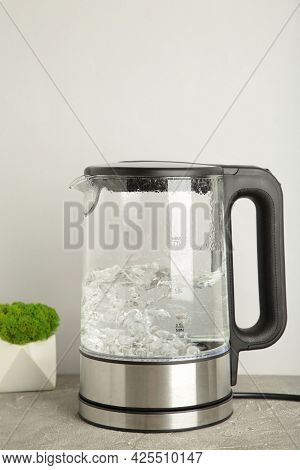 Glass Electric Kettle With Boiling Water On Grey. Top View.