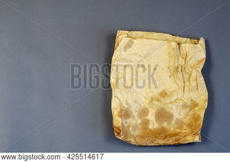 Dirty Brown Paper Bag On A Gray Background. Paper Bag Used For Packing Lunch, Groceries. Recycled Ra