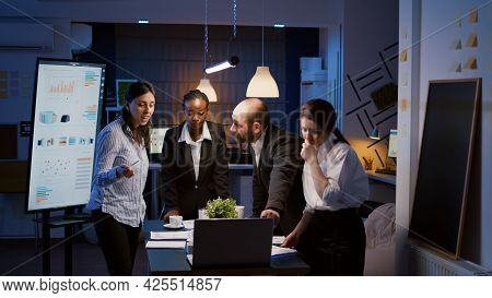 Multi Ethnic Businesspeople Brainstorming Company Ideas Checking Graphs Statistics Using Laptop Stan