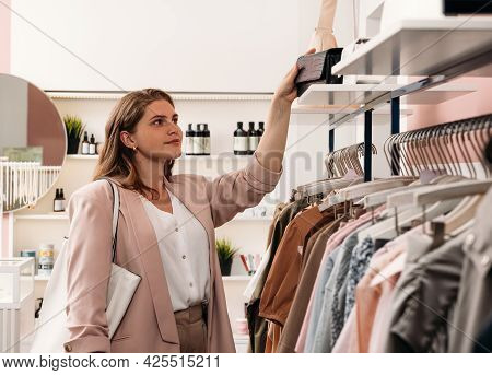 Stylish Woman Takes A Mini Bag From The Rack In The Fashion Store
