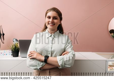 Portrait Of A Young Boutique Owner Standing At Counter. Smiling Female In Her Clothing Store.