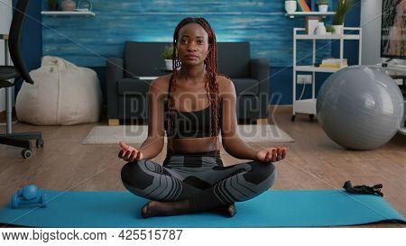 Flexible Flexible Athlete Woman Relaxing In Lotus Position On Floor In Living Room Enjoying Healthy