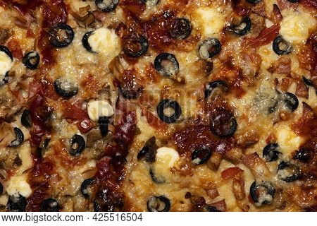 Detail Pizza Made Of Cheese, Olives, Meat, Tomatoes With A Delicious Crust Closeup