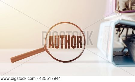 Magnifying Glass With The Word Author On Office Table.