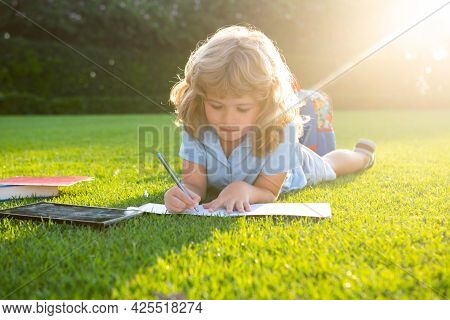 Kid Boy Reading Interest Book And Writing Notes In Copybook In The Garden. Summertime Fun. Cute Boy