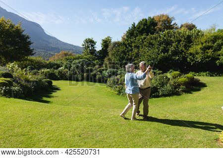 Senior caucasian couple dancing together in sunny garden. retreat, retirement and happy senior lifestyle concept.