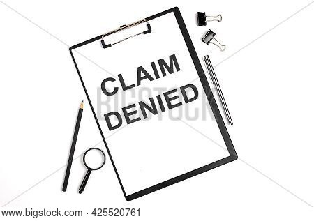 On A White Background Magnifier, Pen And A Sheet Of Paper With The Text Claim Denied. Business Conce