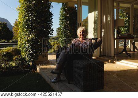 Senior caucasian woman using smartphone in sunny garden. retreat, retirement and happy senior lifestyle concept.