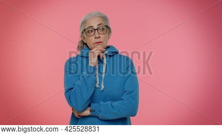 Thoughtful Clever Senior Good-looking Woman Rubbing Her Chin And Looking Aside With Pensive Expressi