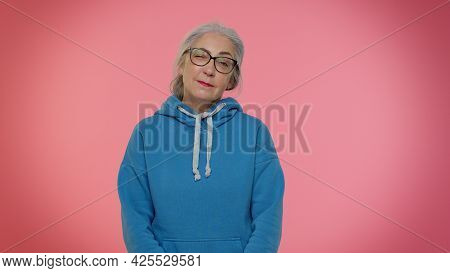 Playful Happy Elderly Good-looking Granny Woman In Hoodie Blinking Eye, Looking At Camera With Tooth
