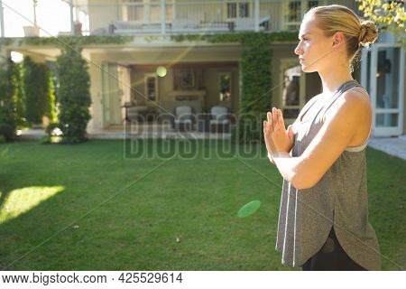Tranquil caucasian woman practicing yoga in sunny garden, standing with hands pressed together. health, fitness and wellbeing, spending quality time at home.