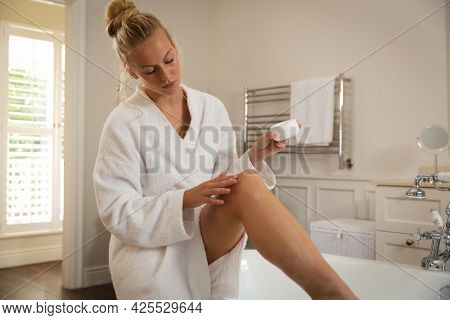 Caucasian woman sitting in bathroom wearing bathrobe moisturising legs. health, beauty and wellbeing, spending quality time at home.