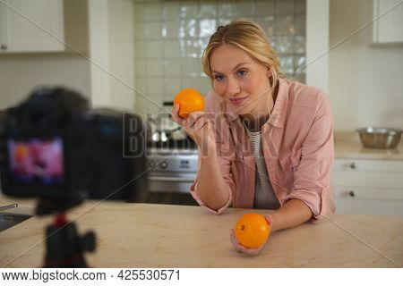 Smiling caucasian woman in kitchen holding oranges and looking at camera, making cooking vlog. technology and communication, cookery vlogger at home.
