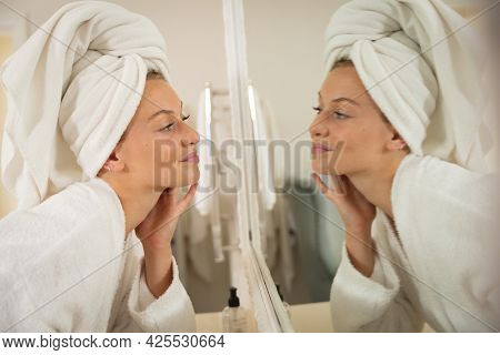Smiling caucasian woman in bathroom with towel on head, looking in mirror and moisturising face. health, beauty and wellbeing, spending quality time at home.