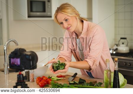 Smiling caucasian woman in kitchen holding vegetables and looking at camera, making cooking vlog. technology and communication, cookery vlogger at home.