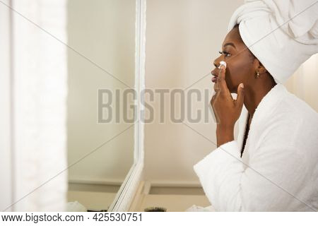 African american woman in bathroom with towel on head, looking in mirror moisturising face. health, beauty and wellbeing, spending quality time at home.