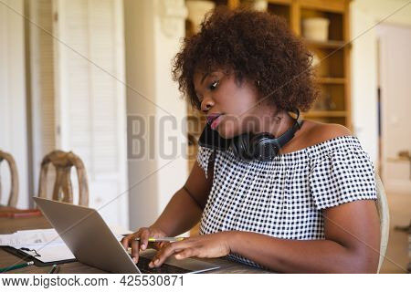 African american woman working in living room using laptop and talking on smartphone. technology and communication, flexible working from home.