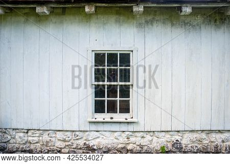 Antique 12-pane Window In The Center Of A Whitewashed Wooden Colonial Building With White Stone Foun