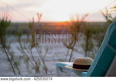 Deck Chair On White Sand With A Summer Hat. Beach With A Deck Chair At Sunrise. Beach With A Sun Lou