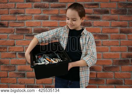 Smiling School Boy Holding A Box With Plastic Robotic Peaces On Brick Wall Background. Ready To Crea