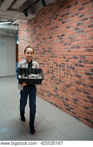 Smiling School Boy Walking While Holding A Box With Plastic Robotic Peaces On Brick Wall Background.