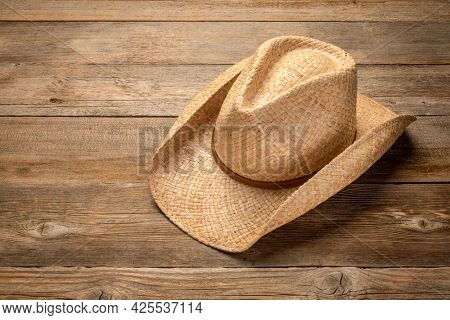 ranch style, cowboy straw hat  on rustic wooden table