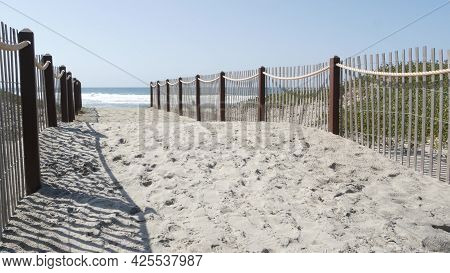 Pacific Ocean Coast, Greenery And Wooden Picket Fence On Sea Shore. Blue Water Waves On Sunny Summer