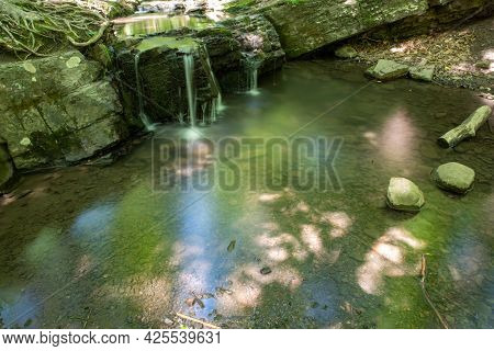 Beautiful Enchanted Forest Scene With Long Exposure Waterfall And Stream Reflecting The Forest Color