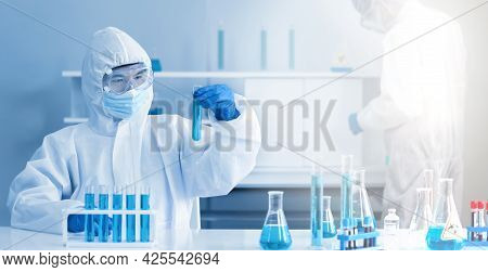 Epidemiological Researcher In Virus Protective Clothing Look At Blue Liquid Chemicals In Test Tube.